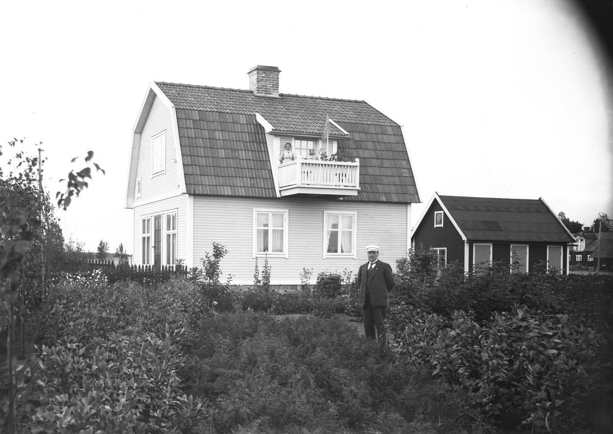 Man utanför bostadshus, kvinna på balkonen.