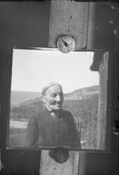 Reprofotografi av en eldre kvinne. Stor brosje i halsen, og