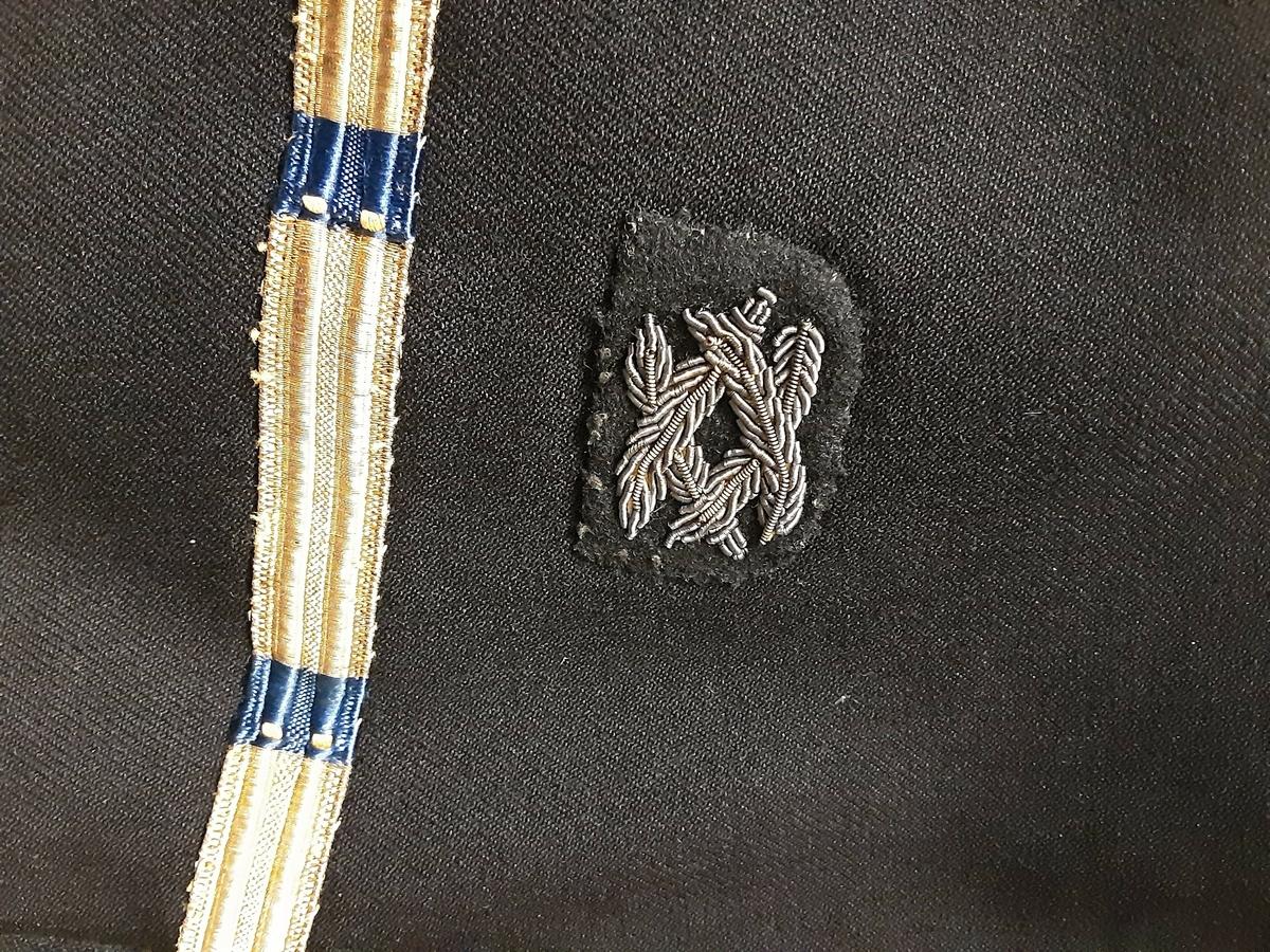 Uniformsjakke tilhørende marineuniform fra 2. verdenskrig. Sort, dobbeltspent med seks gullfargede knapper med ørn i relieff. Nederst på ermet et enkelt gullbånd med blå felter. Over dette båndet påsydd et emblem med små grener.