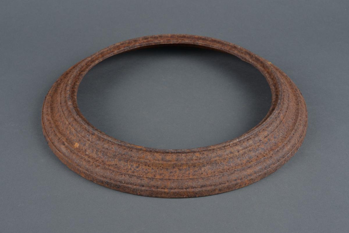 Jernring som har tilhørt en gammel ovn.  Er rund, og skråner inn mot senter av ringen.