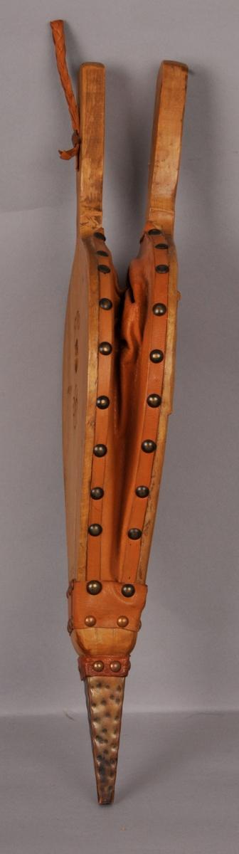 Peispustar i tre og skinn. Koparbeslag og koparnaglar. Håndskoren treskurd med rose og rankemotiv. SMS 1970 skore inn på baksida.