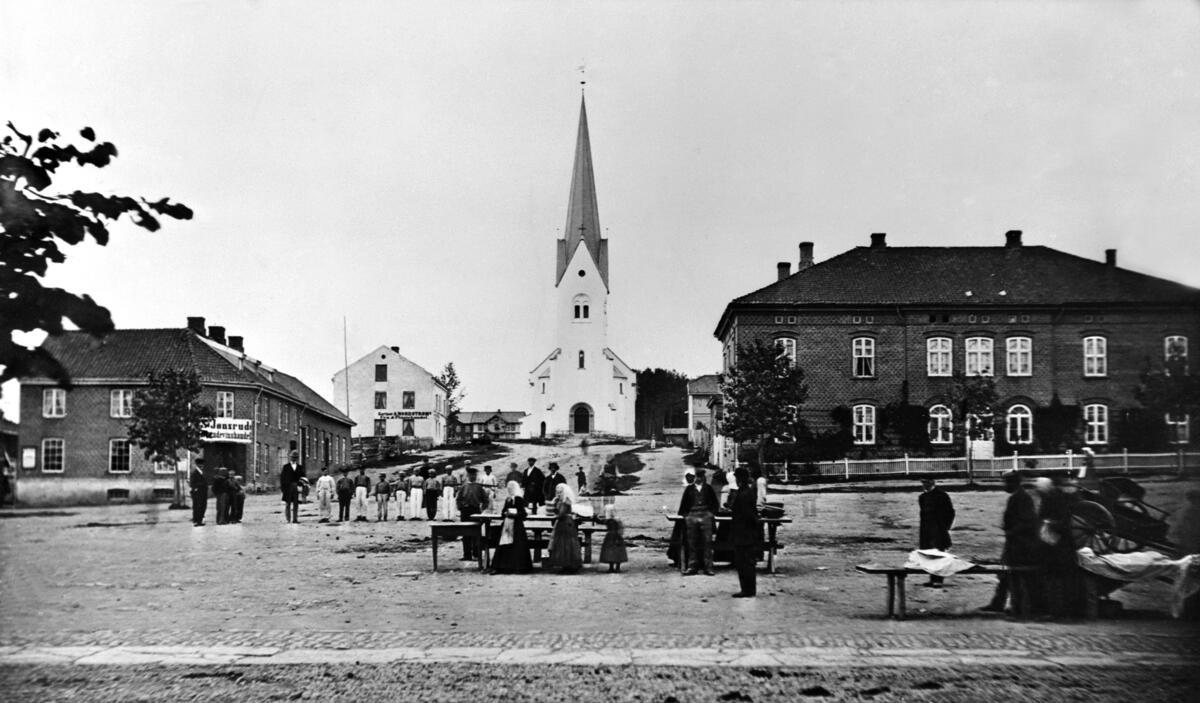 """Svart-hvitt fot som viser et torg med handelsboder og torgkoner i """"gammeldagse"""" klær, et hus i hver bildekant og Hamar domkirke bakerst i midten. (Foto/Photo)"""