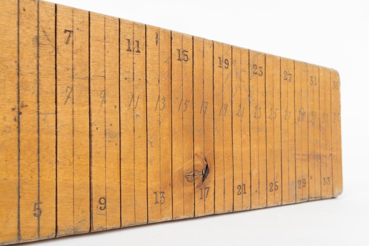 Klavelinjal - altså et vinkelformet redskap til å undersøke stammediametere på stående trær. Det ene vinkelbeinet, som vi her kan kalle «linjalen», er 42,9 centimeter langt og 10,2 centimeter bredt. Det andre vinkelbeinet er gradet inn vinkelrett på det første, snaut 3 centimeter fra dettes ytterende. Det inngradete vinkelbeinet er også festet ved hjelp av to små treskruer. Sentralt i krysningspunktet mellom de to vinkelbeina er det et kvadratisk, gjennombrutt hull, antakelig lagd med sikte på at klaven skulle kunne monteres på ei handtaksstang, slik at redskapet kunne anvendes også i høyder som overgikk brukerens egen rekkevidde. På begge sider av det vinkelbeinet vi innledningsvis omtalte som «linjalen» er det skåret spor i overflata vinkelrett på linjalens lengderetning, på den ene sida med en halv centimeters innbyrdes avstand, på den andre med en centimeters innbyrdes avstand. Linjene er merket med påstemplete tall som forteller avstanden fra det andre vinkelbeinet, som skulle ligge an mot trestammen. Ved å sikte langs de innrissete sporene i linjalen kunne man dermed undersøke stammediameteren utenpå barken. Redskapet er lagd av lyst treverk, som er innsatt med klarlakk. Denne klavetypen skal ofte ha vært brukt under blinking.