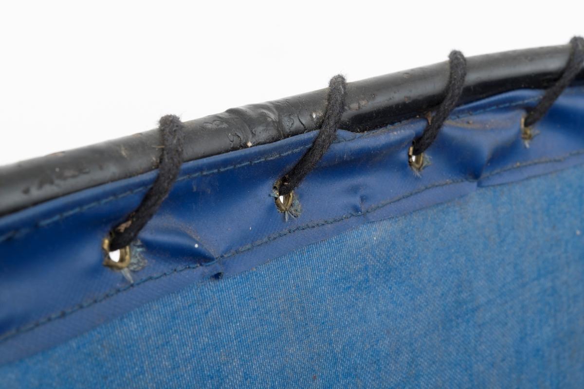 Plantebrett for bæring av barrotplanter under arbeid på plantefelt i skogen. Skjellettet til dette redskapet er lagd av jernrør med 1 centimeters diamter. Rørene er sveiset sammen i ei avlang, litt oval ramme. Utenpå denne ramma er det trukket en presist sydd ytterhud av blått lerretsstoff, som tilsynelatende er plastbelagt på yttersida, på samme måten som på regntøy. Langs overkanten på lerretsbeholderen er det messingmaljer med cirka 4 centimeters innbyrdes avstand, og gjennom disse er det trukket ei svart lisse som - mellom maljene - er tvinnet rundt det jernet som danner overkanten på jernramma. Ramma er noe innsvingt på den ene «langsida», antakelig med sikte på at beholderen skal ligge godt mot plantørens hoftekam. Her er for øvrig ytterhuden forsterket ned et påsydd, dobbeltbrettet rektangulært stykke av det nevnte blå plastdekte lerretsstoffet. Redskapet bæres i cirka 2,3 centimeter brede lærreimer som er festet i overkanten på jernramma. Lengden på disse reimene kunne justeres ved hjelp av nålespenner. En av dem er påtredd ei rektangulær, foret pute med lær på den ene sida og plastdekt lerretsstoff på den andre. Denne komponenten skulle forebygge at redskapet gnog på brukerens skulder.