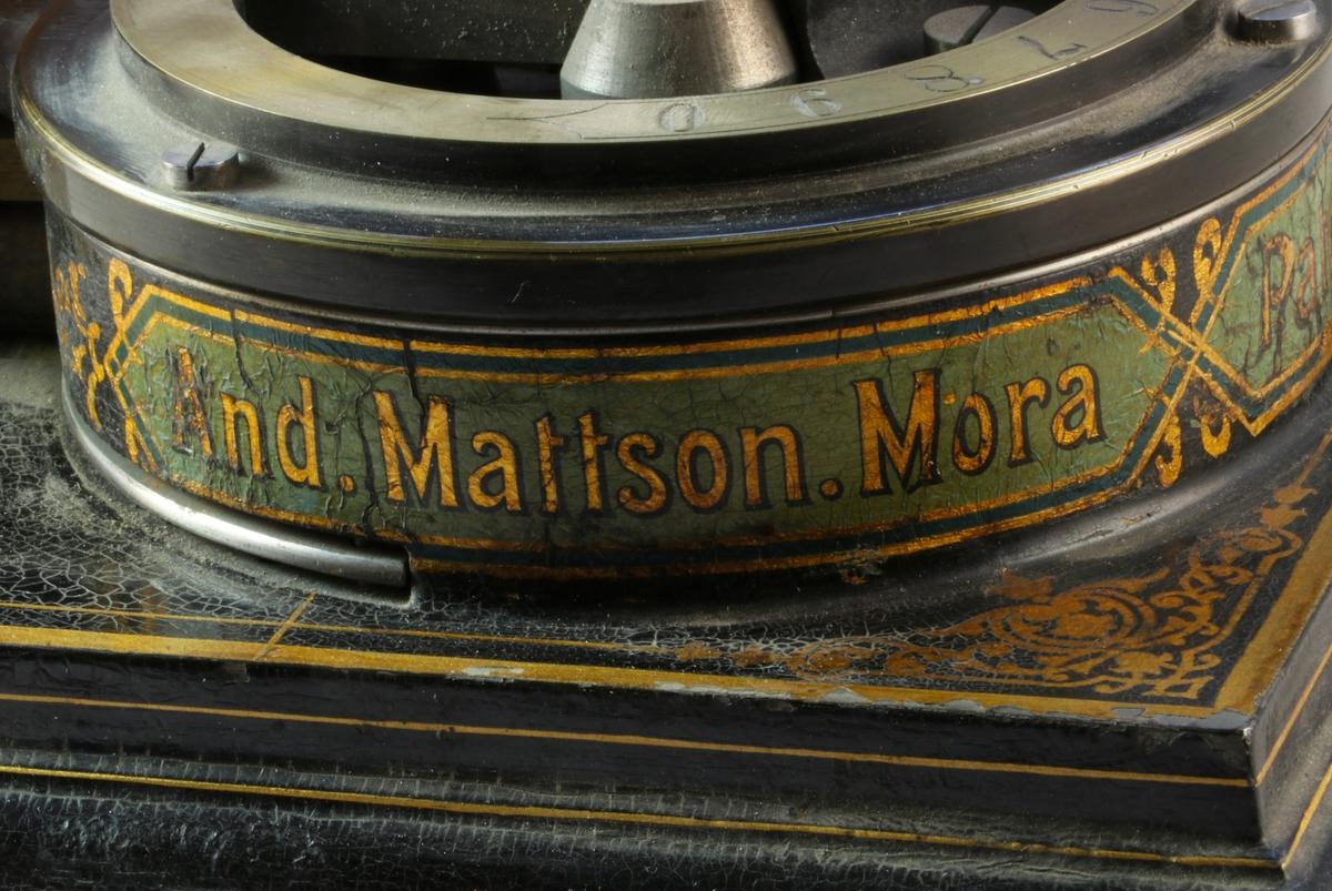 Svart upphöjd platta i metall med målade guldlinjer och dekorationer i guldfärg. Rund metallbricka i svart med mässingsdetalj högst upp. Siffror från 1-0 ingraverade längs med rundeln med spak för att välja siffrorna och perforera. På sidan av rundeln är gulddekorationer samt texten And. Mattson Mora i guldbokstäver med blåmålad bakgrund.