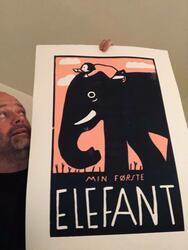 """Kunst av Andreas Brekke. Linotrykk av en liten jente som sitter på en elefant. Under store det """"Min første elefant"""" (Foto/Photo)"""