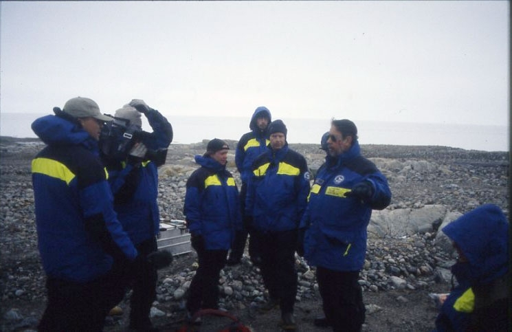 Ett antal personer i polarforskningssekretariates blågula plagg står på Kvitöya (Vitön). En man talar till gruppen. Till höger står en annan man och filmar talaren.