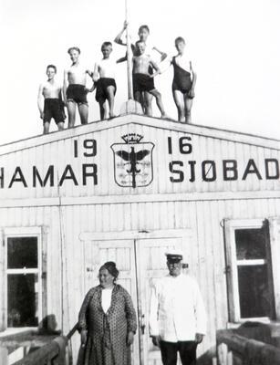"""Hamar sjøbad var et badehus i tre. På dette svart-hvitt fotografiet står bestyrerparet foran døra, mens en gjeng gutter i badebukse poserer oppe på taket. Over døra står det """"Hamar sjøbad 1916"""" og er bilde av Hamars byvåpen (furu med orrfugl). (Foto/Photo)"""