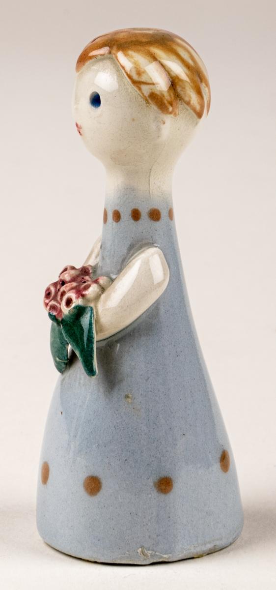 Brudtärna till figuringrupp Brudfölje. Tärnan har ljust hår och ljusblå klänning. Formgiven av Dorothy Clough 1955, Gefle Porslinsfabrik.