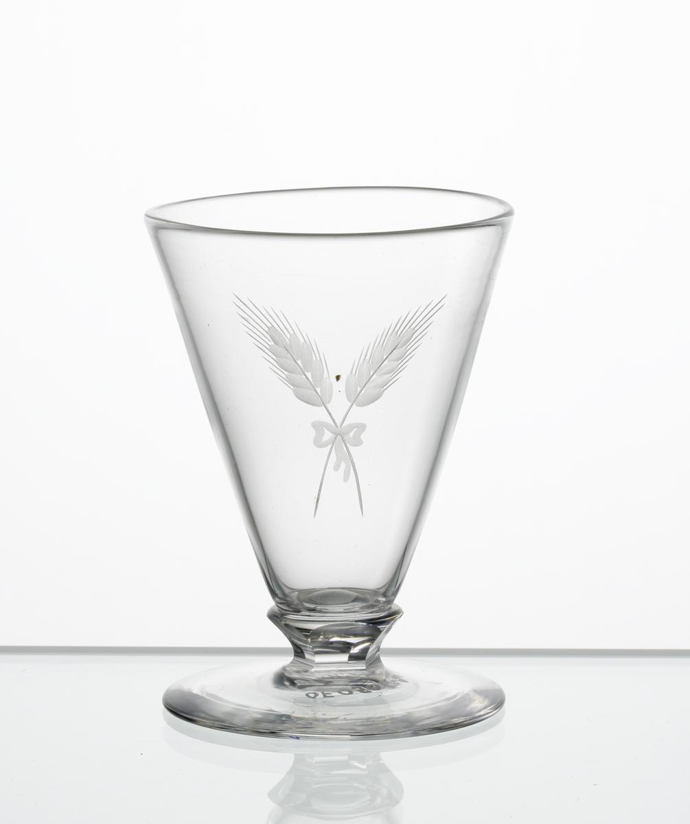 Design: Edward Hald. Brännvinsglas, konisk kupa med fasettslipad knapp mellan kupa och fot. Graverat motiv i form av korslaga sädesax sammanbundna med en rosett, på kupan.
