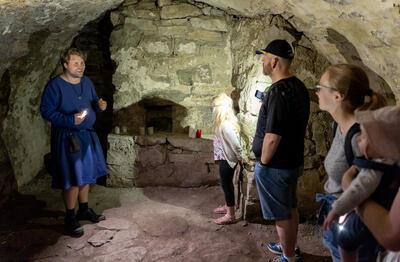 Middelalderkledd guide forteller spennende historier i mørke middelalderkjellere.. Foto/Photo