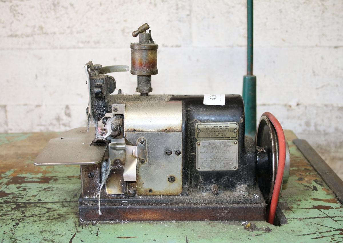 """Overlockmaskin. Symaskin, infällt i grönmålat träbord med motor och trampa. Användes för att sy ihop vävmaterial, med medlöpare för tryck- och beredningsmaskiner. För att få långa körningar i tryck, färg, beredningsmaskiner och spannramar. Dekatur. Märkt: Merrow Machine Co...... Proveniens Rydboholmsbolaget AB, samt senare Rydboholms Textil AB, Rydboholm.  Historik: Rydboholms historia går så långt tillbaka som till 1830-talet, då Sveriges störste industriman inom textilen, Sven Eriksson, grundade Rydboholmsbolaget.  Under slutet av 1800-talet växte Sveriges första stora textilbolag upp i trakterna runt Borås. När bolaget var som störst sysselsatte det ca 1500 anställda, på spinneriet i Rydal, väveriet i Viskafors och på färgeriet/tryckeriet här i Rydboholm. Sven Eriksson importerade även de första textilmaskinerna till Sverige. Företaget blev ett med bygden och tillhandahöll såväl skola som åldringsvård och kyrka. Det var inte ovanligt att arbetarna och deras familjer levde hela sitt liv i och omkring fabriken som utgjorde navet i hela samhället.  Rydboholmsbolaget levde vidare till 1982 då det lades ner efter en konkurs. Då flyttade """"Linds Färgeri & Tryckeri"""" in i den gamla Rydboholmsfabriken. Tio år senare bytte företaget namn till Rydboholms Textil AB.  De nya ägarna hade erfarenhet från Strömma Textil. Huvudbolaget NIFE Textil AB, ägde bifirmorna Rydboholms Textil, Ljungbergs Textiltryck i Floda och Berners Textil."""