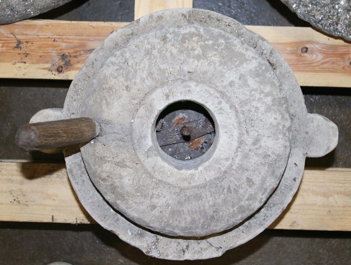 """Handkvarn, saltkvarn. Kalksten. Rund. Består av två delar, """"liggare och löpare"""". Liggaren med två utstående öron. Överdel något välvd, med centralt hål samt träpinne på sidan för att röra om."""