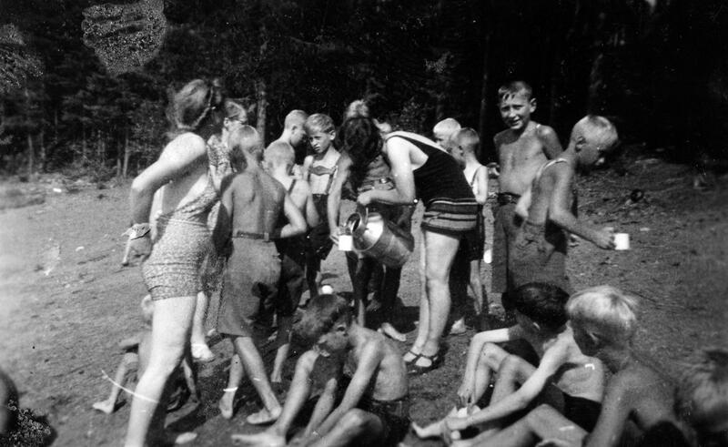 Gutter fra Borgen feriekoloni på badeplassen ved Fangberget i Mjøsa, 1940. Saft er medbrakt på melkespann og serveres til barna. De voksne som er med på turen er bestyrerinnen, kokka og stuepiken. Foto: Anno Domkirkeodden. (Foto/Photo)