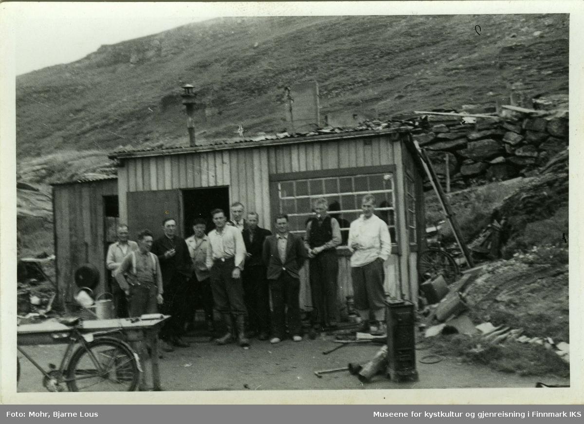 Gruppebilde av ti menn foran en brakke i Hammerfest. Mannen med hvit skjorte som står i midten, er Hans Heggelund. Til venstre står et bord og en sykkel. Til høyre av brakken ser man en mur og i bakgrunnen ligger Salenfjellet.