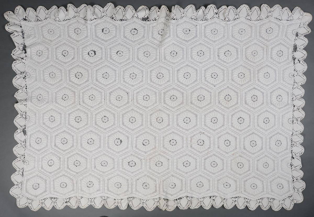 Heklet teppe med 6-kantede rosetter med en opphevet 18-bladet rose i midten. Den har 24 opphevede knopper i ytre kant av rosetten. Tunger rundt alle sider på teppet.