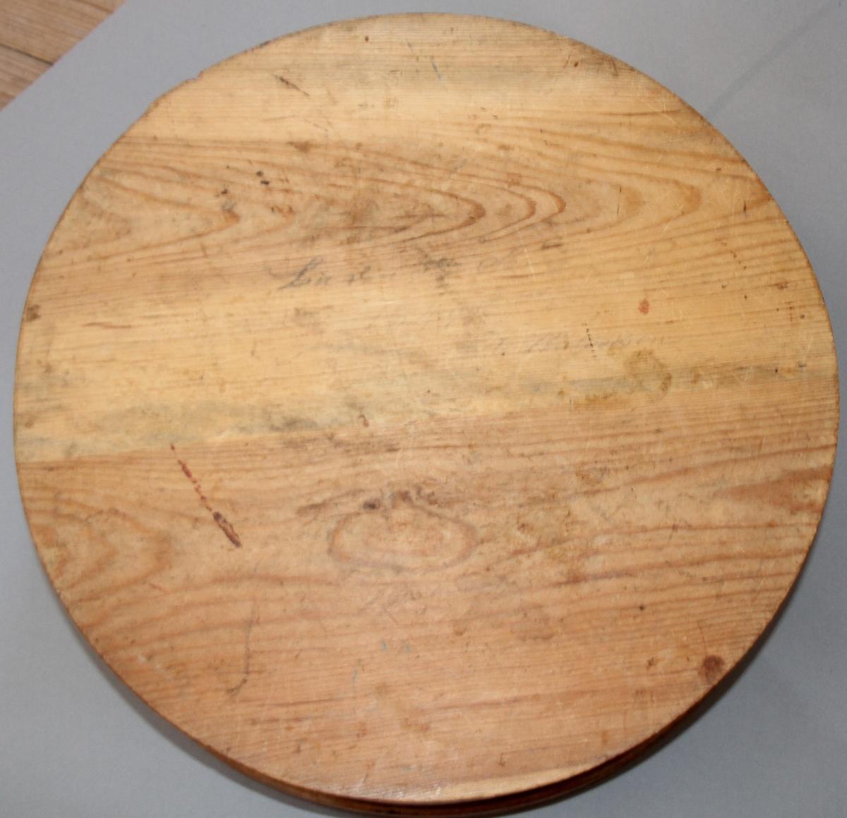 Rund ask med lok. Sveipa. Ådringsmåla. Loket har ein kant som går utanpå sjølve asken. Utydleg blyantskrift under botn.