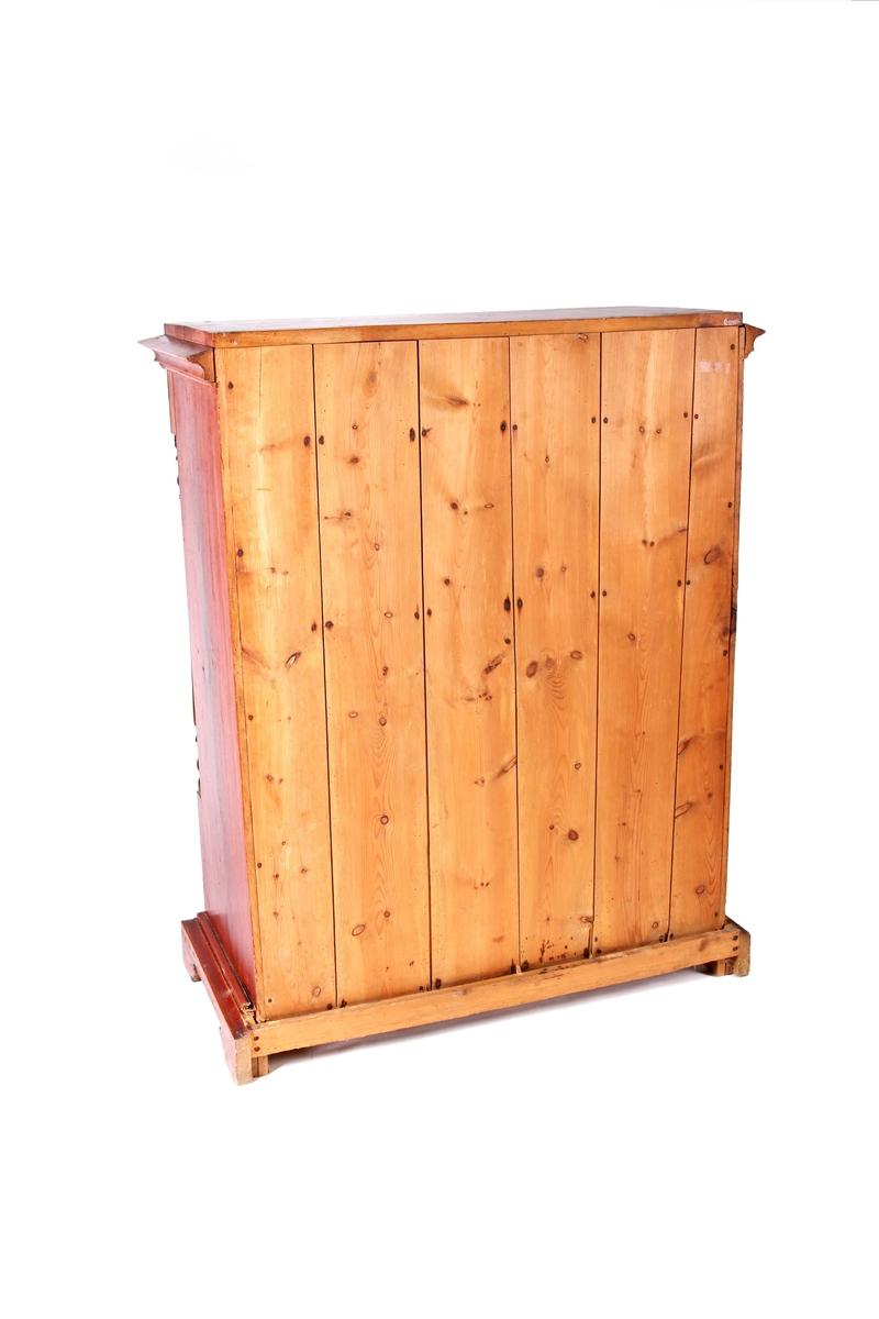 Rødbrun skatoll med skriveklaff i front. Brune rundsøyler på hver side av skriveklaffen. Tre langskuffer under og en langskuff over. Nøkkeskilt i hvitt elfenben.