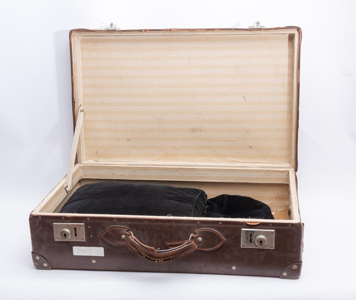 Kofferten har inneholdt alle smågjenstandene brukt til seremonier i Oslo Kvinnelige Handelsstands Forenings orden Dona Mercuri. Alle disse gjenstandene har fått registreringsnumrene KMR.03841 tom. KMR.03864