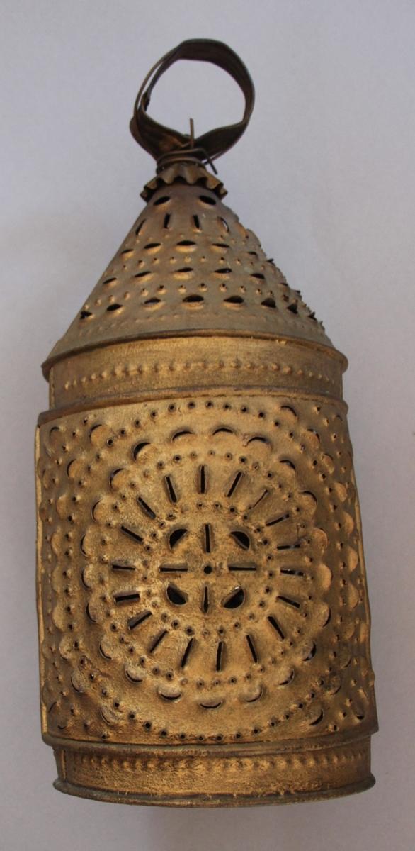 Stakkevarmar i metall. Sylinderforma med kjegleforma topp og ring til håndtak på toppen. Den har ei mengd hol der varmen kan koma ut. Plass til lys inni. Handtaket er forsterka med ein metalltråd.