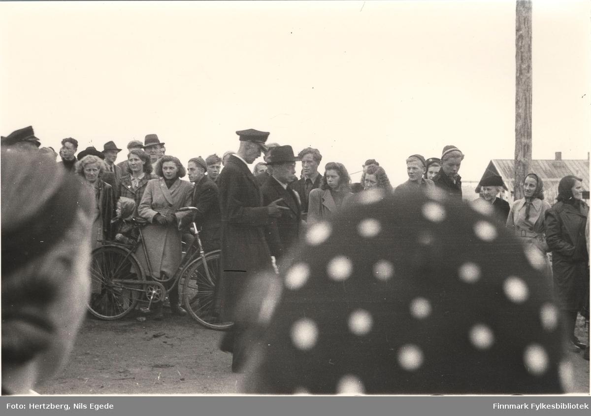 Kong Haakon VII på besøk i Vadsø i 1946. Til høyre siden går fylkesmann Hans Julius Gabrielsen. Mange mennesker har kommet til stede for å se på kongen. Se også bildene 264-267.