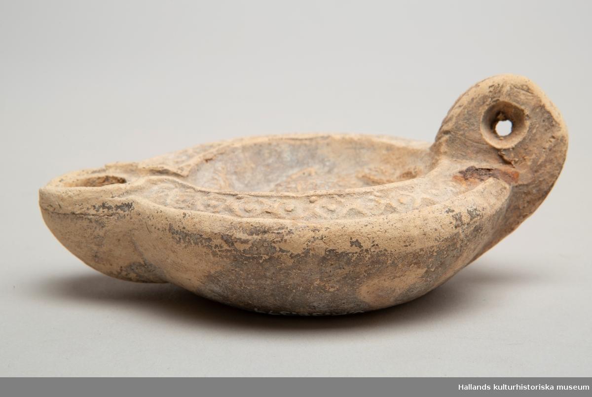 Oljelampa av keramik. Rund med pip i ena änden och ett uppåtstående handtag i den andra. Hål genom handtaget. Två mindre hål i mitten. Motiv bestående av en fågel med en krans i näbben i mitten och cirkelornamentik omkring. Pipen något nött.