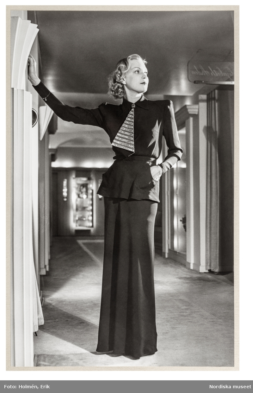 Mannekängen Margit Langlet visar plagg i salongen på NK:s Franska damskrädderi, med klassicistisk dekor. Klänning med skjortblusliv medmarkerade axlar, lång smal ärm och skärp i midjan. I halsen en mönstrad kravatt. Hellång, smal kjol.