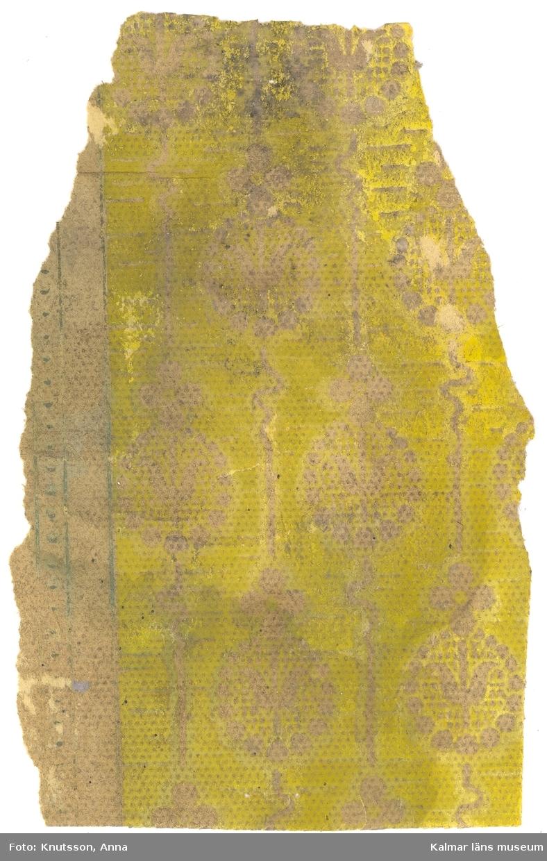 KLM 44014:6 Tapet i papper. Det är en jugendtapet med små täta medaljonger med stiliserade blommor i, bakgrunden är gul, medaljongerna är i pappersfärg. Det finns också lite guld i trycket.