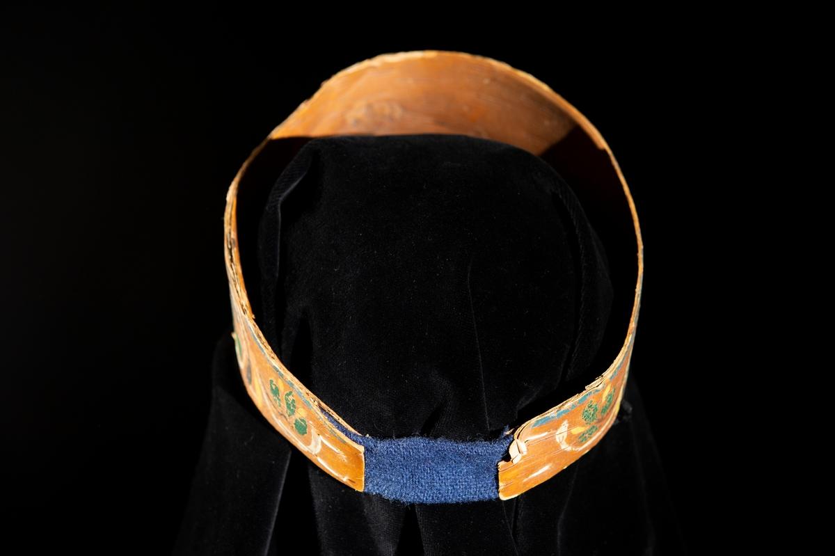 Symmetriskt mönster målat på näver, som hophålles av blått ylleband.
