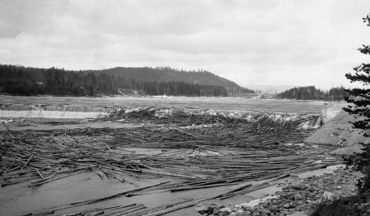 Tømmervase på dammen ved Skjefstadfossen, Elverum, Hedmark. Glomma. Bru i bakgrunnen av bildet.