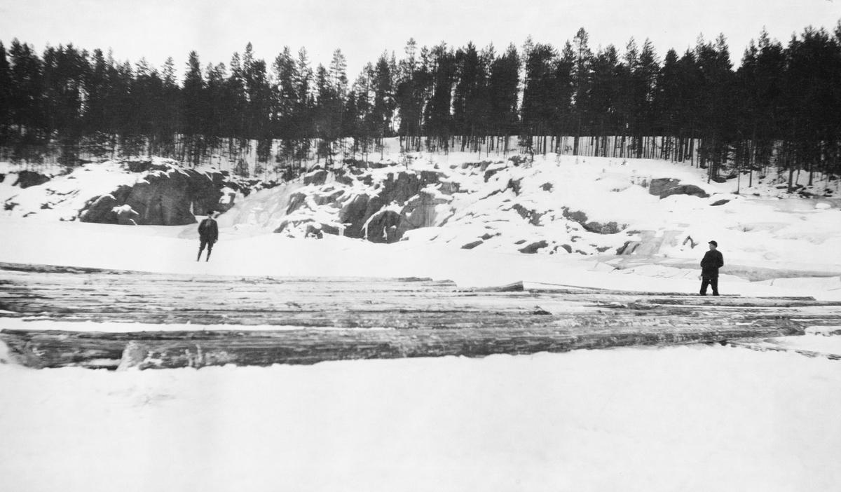 Tømmer på snø og is. Lapstuen og O. Bjørneby. Glomma ved Fossvika, Braskereidfoss, Våler, Hedmark.