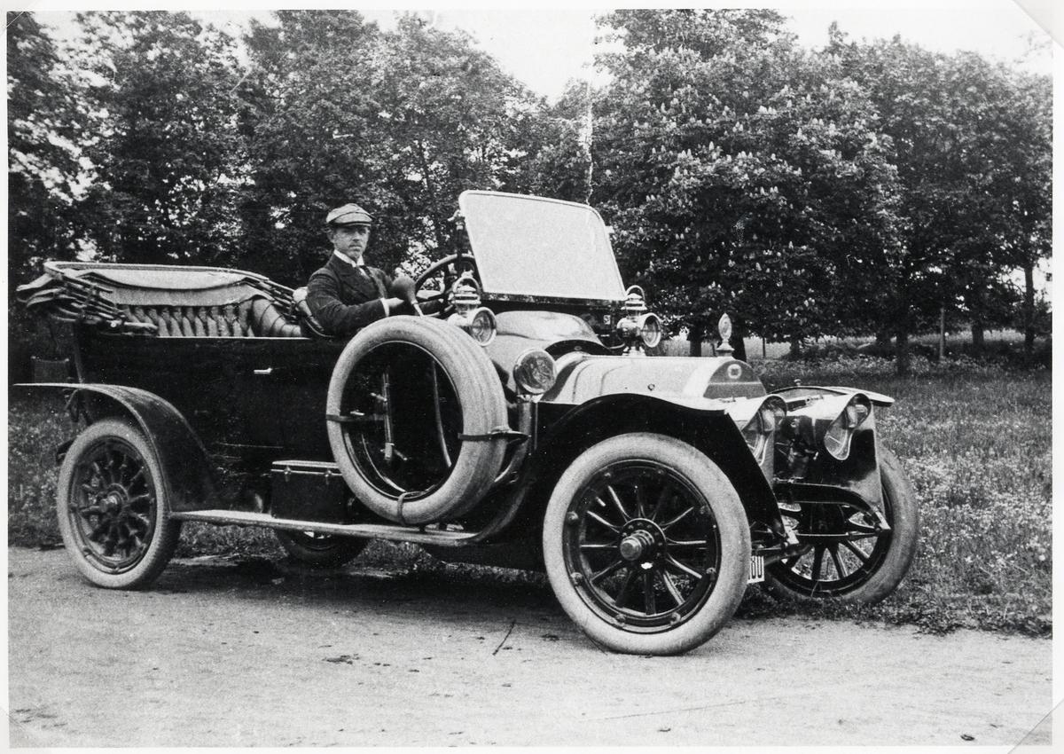 En man i kavaj och keps poserar i sin bil, parkerad på en grusväg vid Kronobergs kungsgård, ca 1920.  Bilen är en Fiat 20/30 HP från ca 1911. Den köptes från Fiatåterförsäljaren AB Wiklunds i Stockholm, och registrerades den 8:e januari 1912 på registreringsnummer A1480. Vid den revidering som gjordes av bilregistret 1916 fick denna bil den 29:e februari 1916 registreringsnummer G15. Torsten Ohlsson ägde bilen fram till 1923.  Torsten Ohlsson (1891-1934), son till landskamrer Fritiof Ohlsson, Växjö.  Student i Växjö 1910. Löjtnant vid Kronobergs regemente, bosatt på Kronobergs kungsgård. Gift 1917 med Irma Hilda Emma Lindén (1893-1972) fr. Växjö.