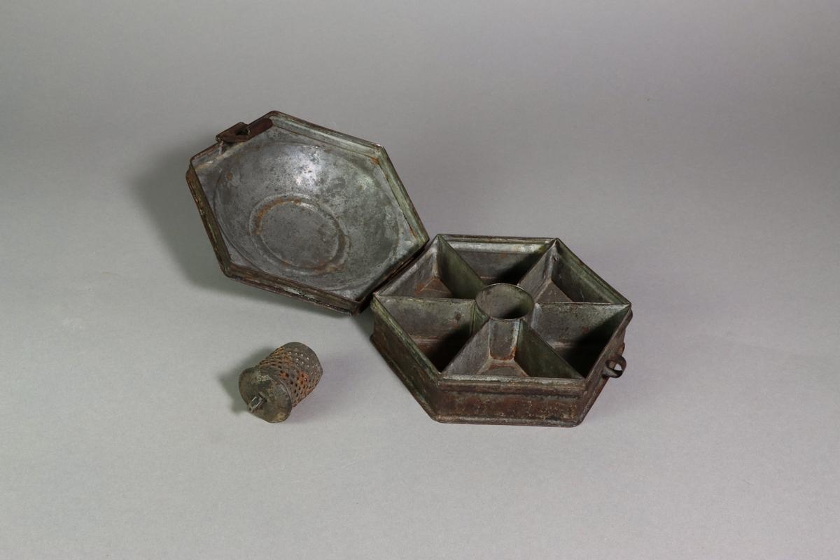 Skrin av metall med sexkantig form och ett tillhörande litet cylindriskt rivjärn. Välvt lock krönt av en ögla. Locket är baktill fäst med ett gångjärn. Skrinets sidor är dekorerad med en profilerad list. Fram på skrinet finns en hänkel för låsning. I skrinet finns sex triangelformade fack och i centrum en rund hållare för ett rivjärn. Cylinderformat rivjän med välvd överdel och en omvriden genombruten knopp av pålödd bläckplåt.