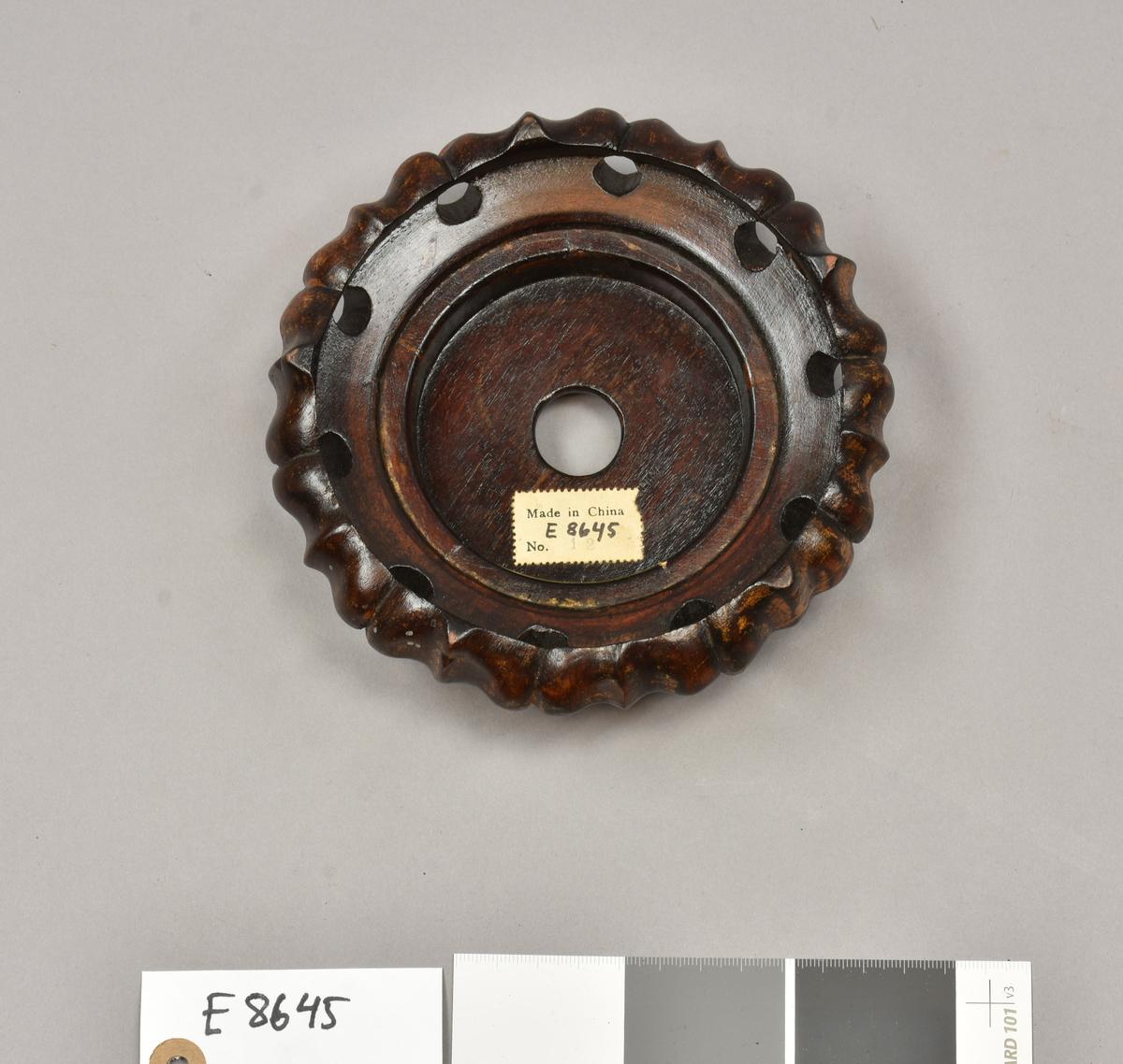 """E 8645 Fra protokollen: """" Sokkel av tre, rund. D: 15,6 cm, H: 5,1 cm. Kina, Øst-Asia. Sokkelen er lakkert brun. I bunnen er det risset inn """"CHINA"""", i tillegg til at den har et hull gjennom senter. Den er også merket med en papirlapp med teksten """"Made in China"""", gjenstandsnummeret og """"No. 12"""". På utsiden er det utskjærte blader, med runde hull mellom."""""""