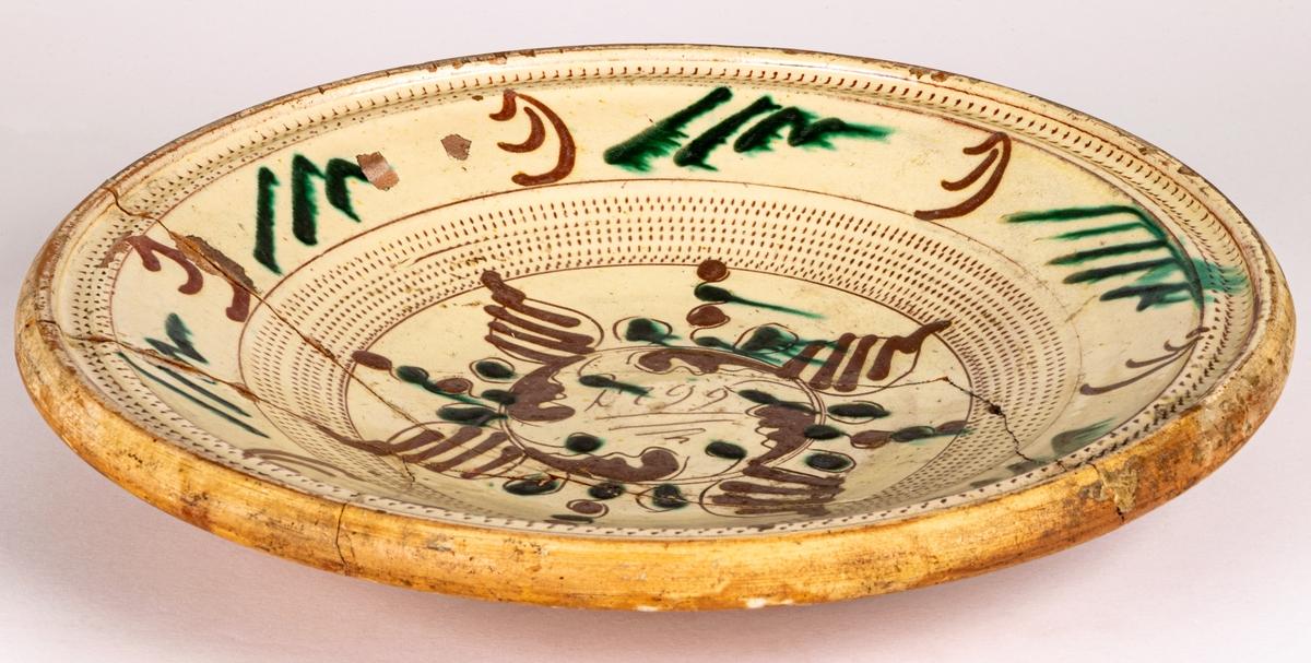 Lerfat, invändigt glaserat i gult, dekor i brunt och grönt. 1799, spräckt.