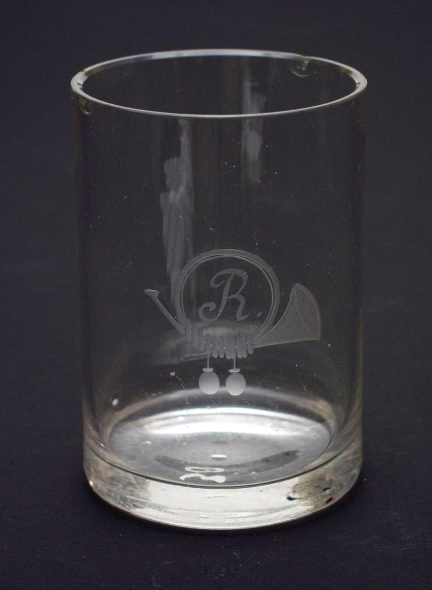 Sylindrisk glass med kraftig bunn. Inngravert et horn med to dusker og bokstaven R.
