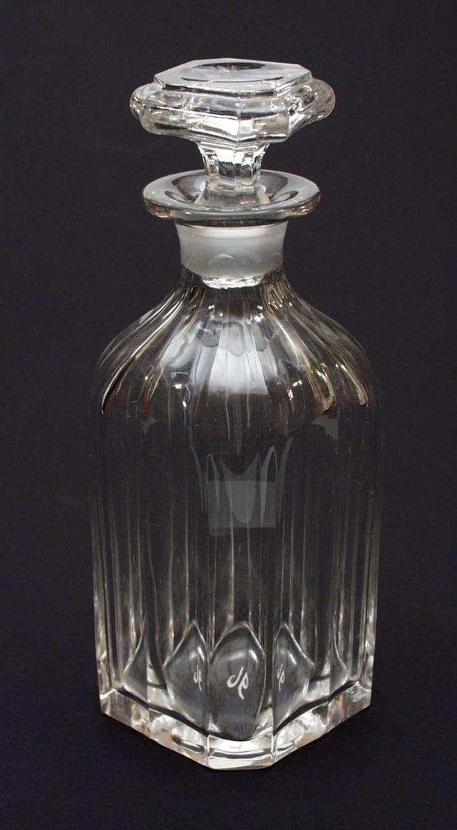 Flaske i krystall med fingerbrede fordypninger fra hals til bunn.