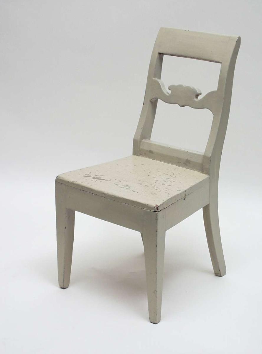 Liten gråmalt stol i gran med utskåret ryggstykke. Stolen har glatt skulderstykke og firkantede ben - forben rette, svungne bak. Setet smalner bakover.