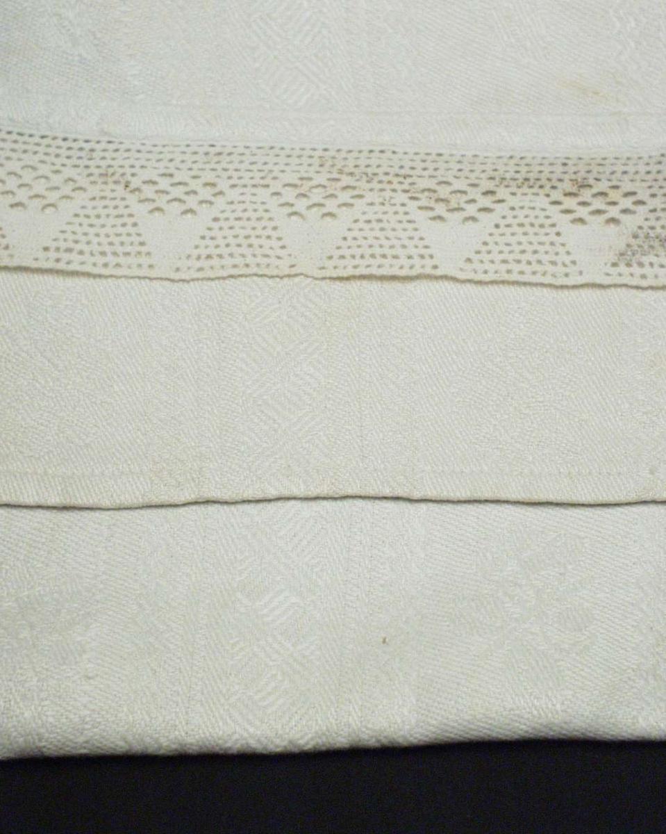 Hvit linduk, faldet med maskin og påsydd med hånd en blonde i ene enden. Vevbredden er 45,5 cm. Lintøyet er stripete med border i lengderetningen. 4,5 rapport i bredden. Mellom, fast, rettvinklet oppbygd mønster med kryssfigurer, 5,5 bred er et felt med blad-og blomstmotiv hvor alle vender samme vei.