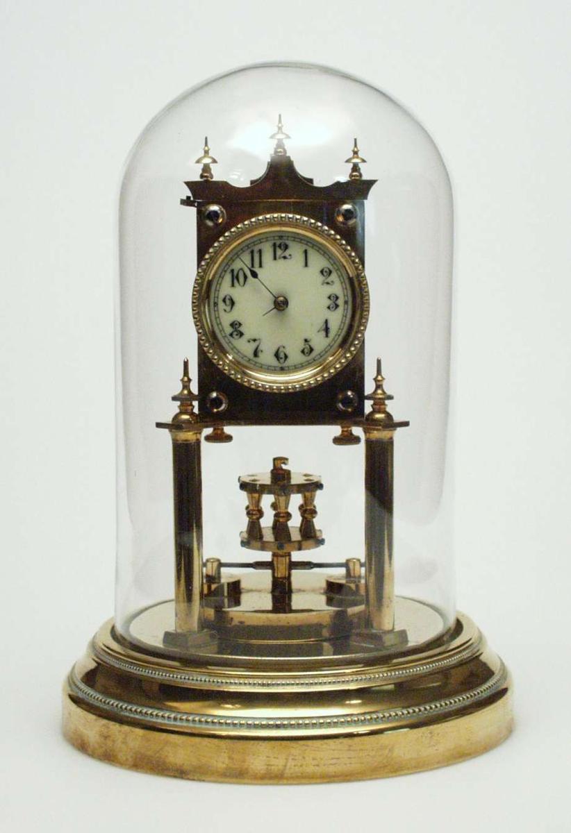 Bordur i messing med glasskuppel. Det går et år av gangen. Uret har rundt understell med perleborder.