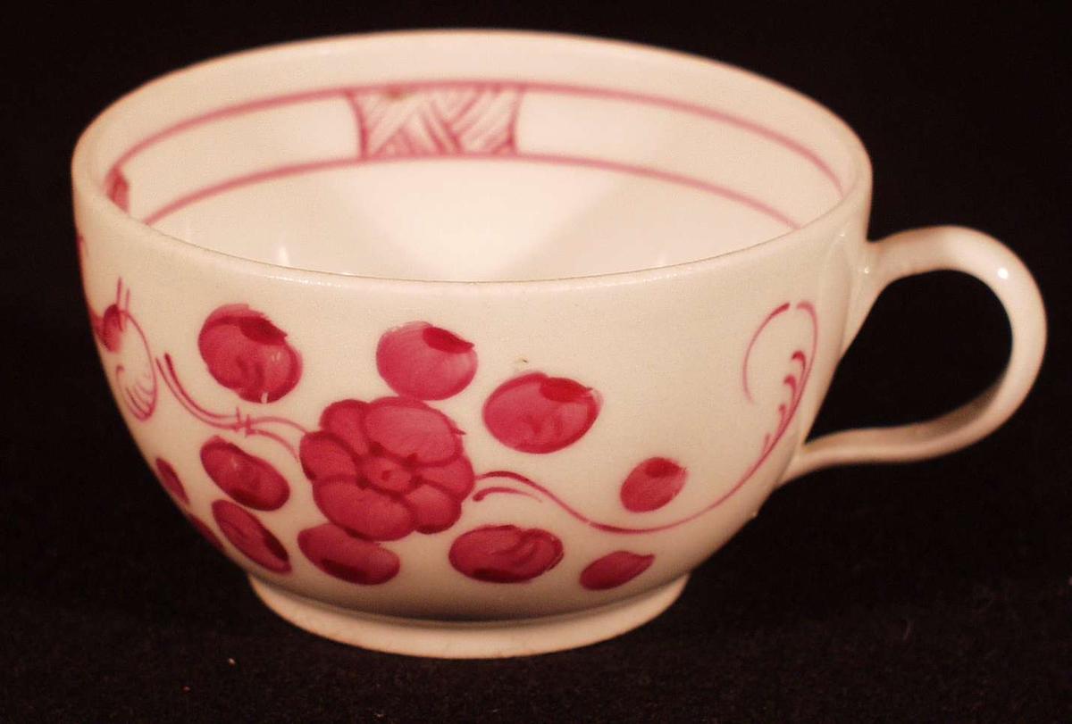 Coupeformet m. hank og lav fotrand. Rødlige blomster. Fugler og grener på utside. Innvendig har koppen har en liten blomst og 2 smale linjer om kant m.2 motstilte  firkanter m. nettverk, 2 m. fylte ringer.