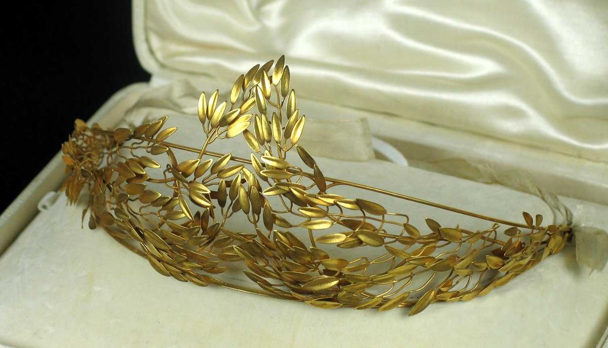 Myrtekrans i gull med hvitt silkebånd bak.
