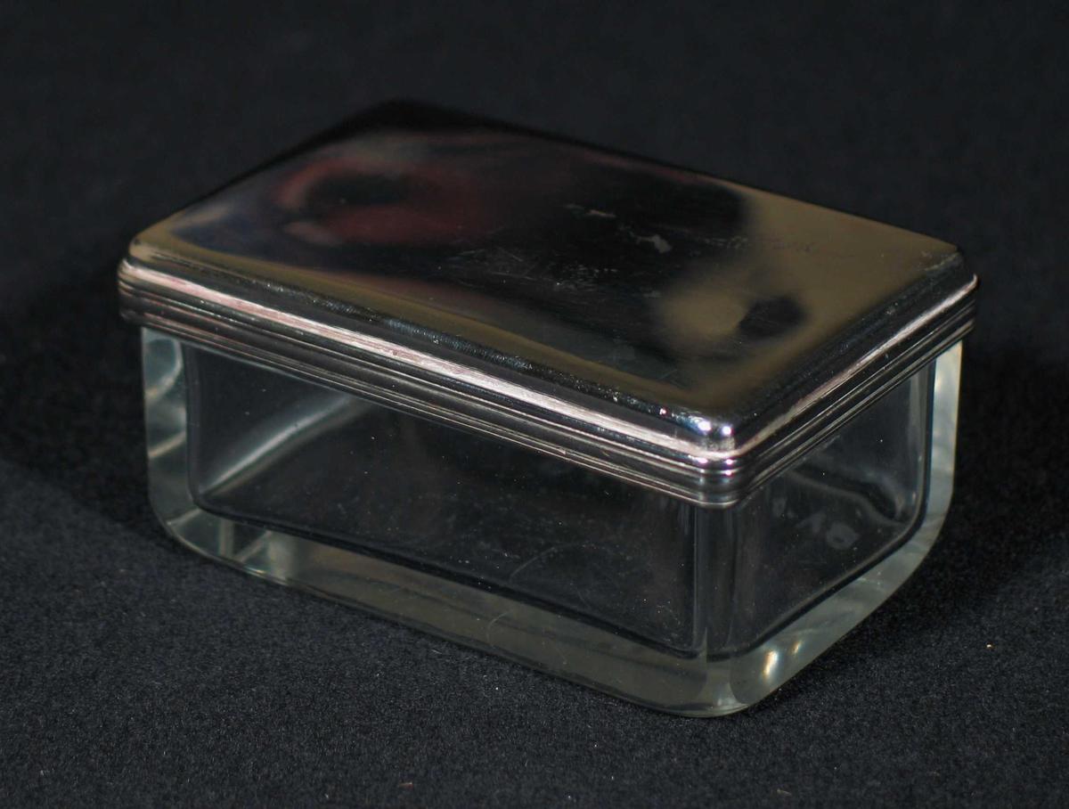Rektangulær såpekopp i glass med lokk av metall.