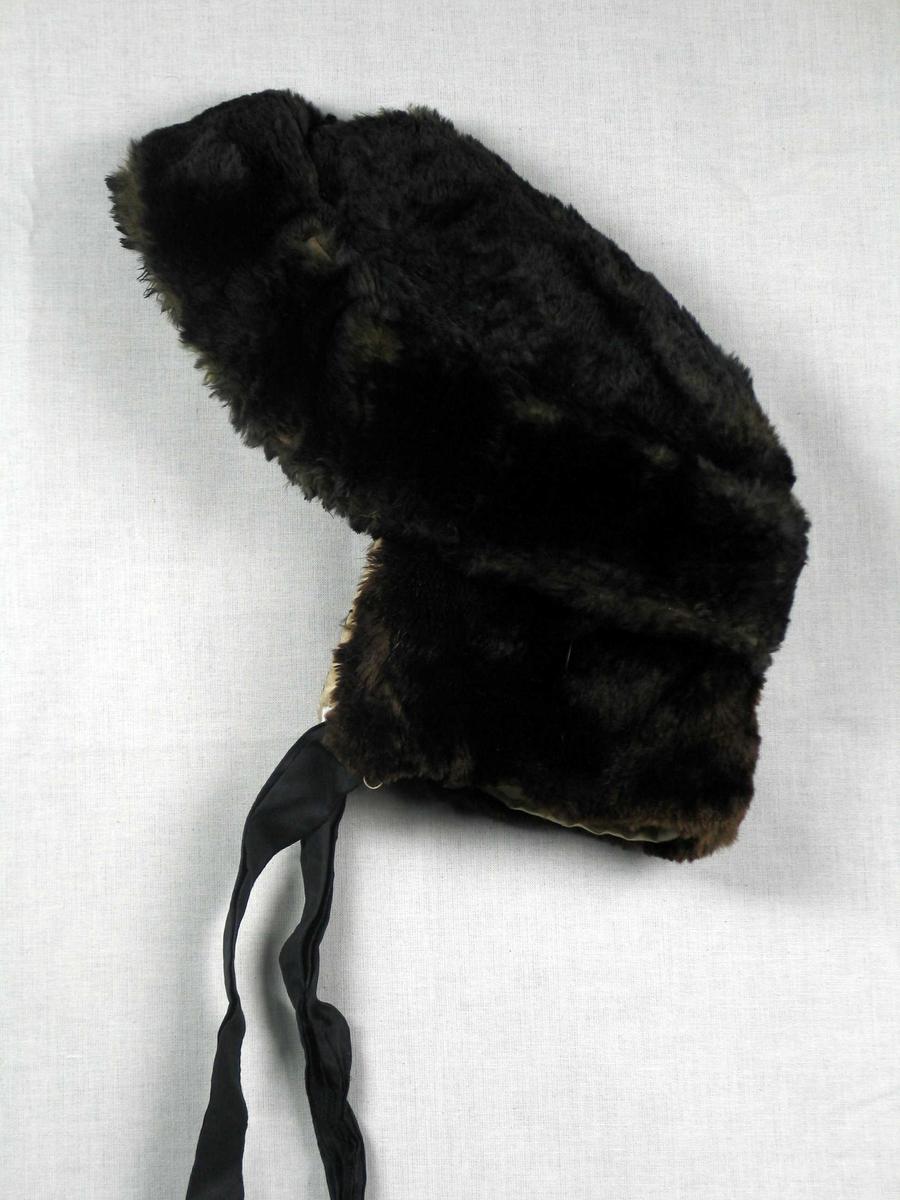 Mørk brun lue i bisampels med bengult fôr i natursilke. Luen har svarte silkebånd. Den er ovalt formet med grunn pull, 5 cm bred oppbrett og nedbrettet nakkeklaff. Fôret er satt sammen av fire stykker. Luen er håndsydd. Buntmakerarbeide?