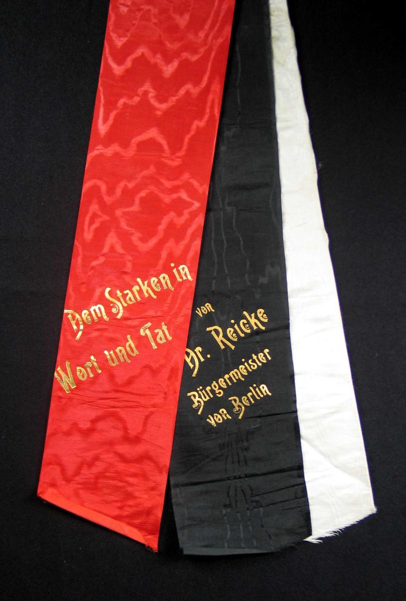 Begravelsessløyfe i rød, svart og hvit silke med tekst i gull.