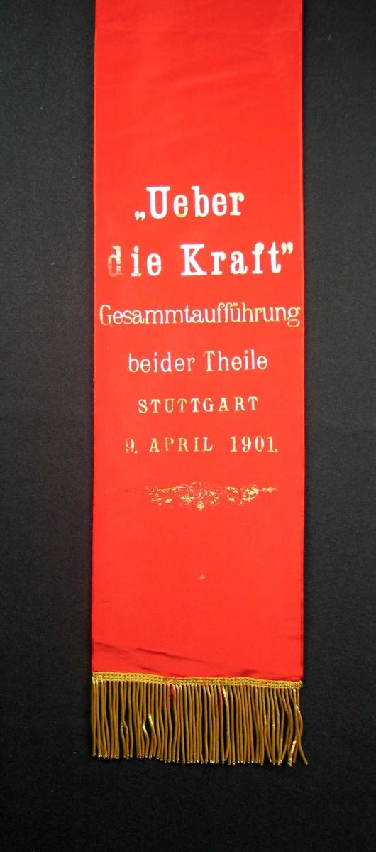 Begravelsessløyfe i rød silke med tekst og frynser gull.