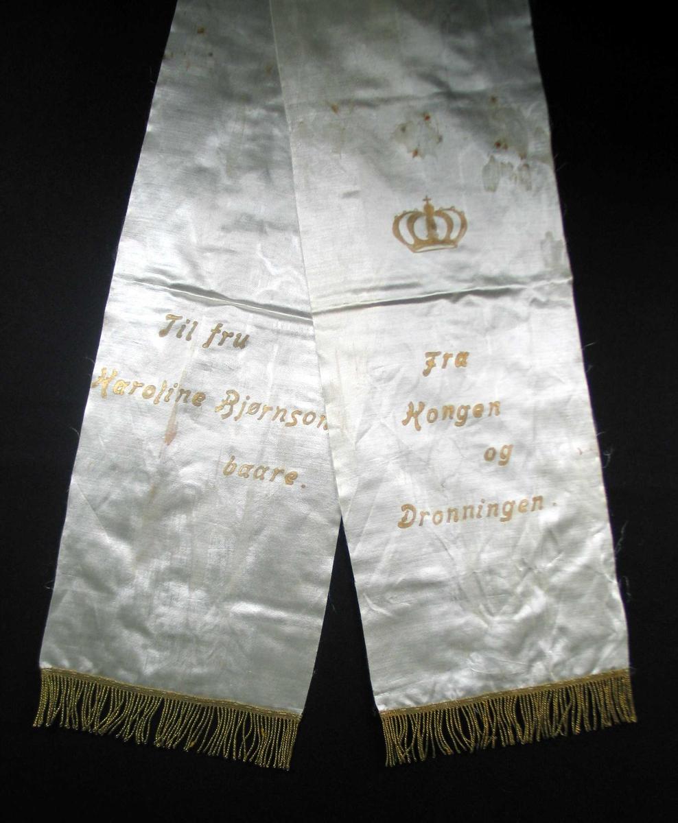 Begravelsessløyfe i hvit mønstret silke med tekst og frynser i gull.