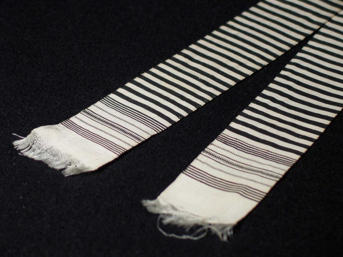 Tverrstripete silkebånd i svart og hvitt. Hvite frynser i begge ender dannes av renningen. Innslagsutglidning ved frynsene. Vevbredden er 4,5 cm.