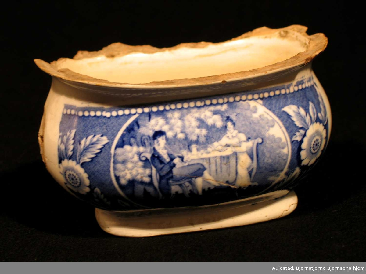 Hvit vase i steintøy med blå dekor. Motivet er en hagescene og blomster. Vasen har vuggeform med fotstykke og utoverbrettede kanter (defekte) På siden ti hull.