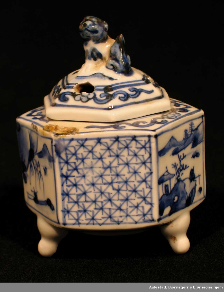 Sekskantet røkelseskar i porselen med tre små bein, hvit underglasur og blå overglasur. Karet er sekskantet der felter er dekorert med landskap og kryssmønster. Hundefigur på toppen.